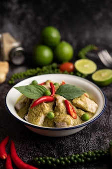 Pork green curry in a white bowl with spices on a black cement background