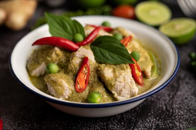 Curry di maiale verde in una ciotola bianca con spezie su uno sfondo di cemento nero