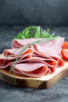 Pork ham slices on cutting board over dark background