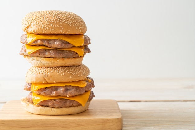 목판에 치즈를 얹은 돼지고기 햄버거 또는 돼지고기 버거
