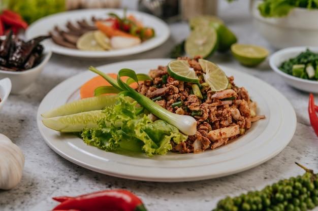 Ларб из свинины с морковью, огурцом, лаймом, зеленым луком, чили, свежемолотым перцем и листьями салата.
