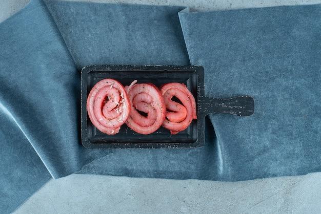 Lardo di maiale su una tavola su pezzi di tessuto, sul tavolo blu.
