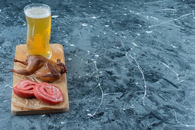 青いテーブルの上にまな板の上にポークラード、グリル、ビール。