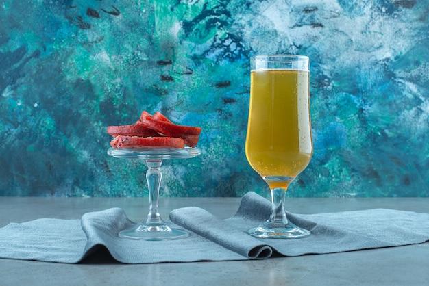 Сало свинины на стеклянной миске и стакан пива на куске ткани на синем столе.
