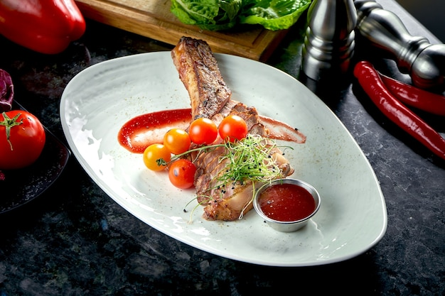 Pork loin steak on the bone with cherry tomatoes and red sauce, served in a white plate. dark marble table. barbecue meat, restaurant food.