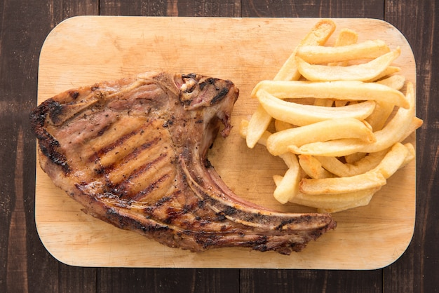 Pork meat grilled and french fries on wooden table.