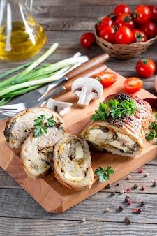 버섯과 치즈로 채워진 돼지 고기 롤은 나무 보드에 야채와 함께 제공됩니다.