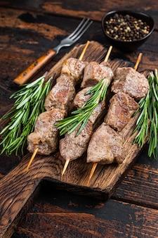 木の板にハーブを添えた串焼きの豚肉シシカバブ