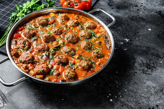 Котлеты из свинины с томатным соусом и овощами на сковороде