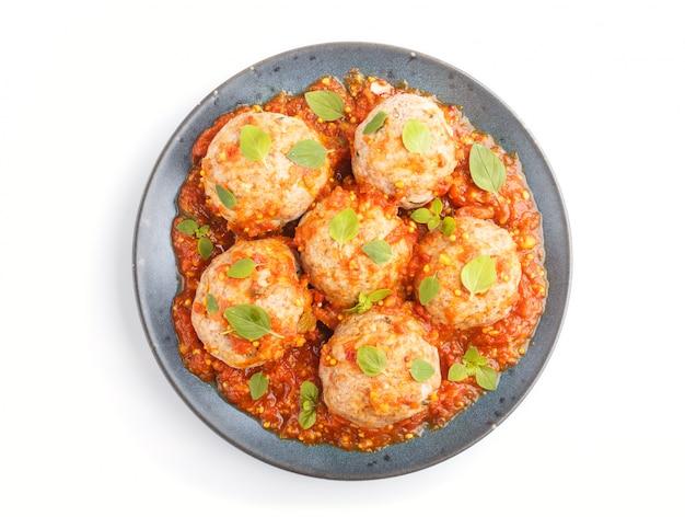Фрикадельки из свинины с томатным соусом, орегано, листья специй и трав на синей керамической тарелке на белом фоне