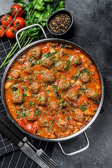 Pork meatballs with tomato sauce and vegetables in a pan. black surface. top view