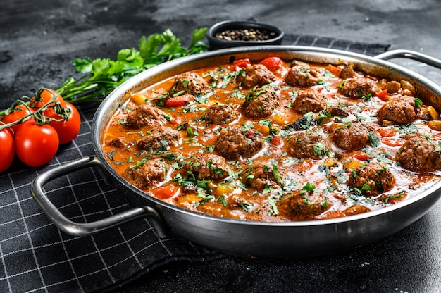 Pork meatballs with tomato sauce and vegetables in a pan. top view