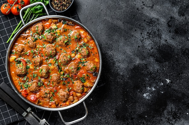 Pork meatballs with tomato sauce and vegetables in a pan.