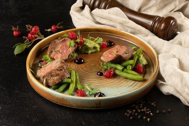 Медальон из свинины со спаржей и гороховым пюре. горячее мясное блюдо с овощным гарниром