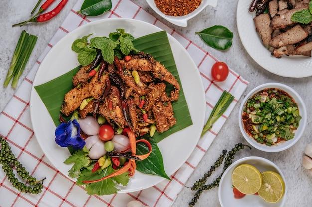 揚げ唐辛子、トマト、ライム、きゅうり、新鮮な唐辛子を添えたポークナムトック。タイ料理。