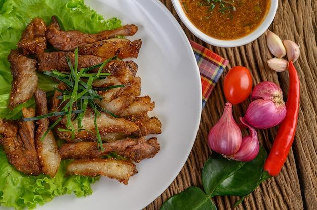 붉은 양파, 토마토, 칠리 나무 테이블에 하얀 접시에 돼지 고기 목 구이.