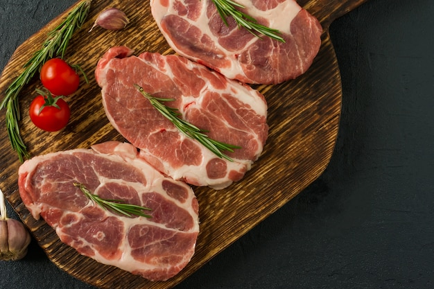 Сырое мясо свиной шеи для свежих стейков отбивных на деревянной разделочной доске. вид сверху.