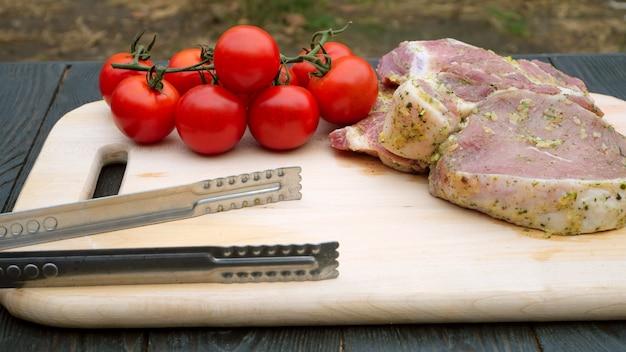 Стейки из свинины или говядины, маринованные в специях для жарки, и помидоры черри на ветке.