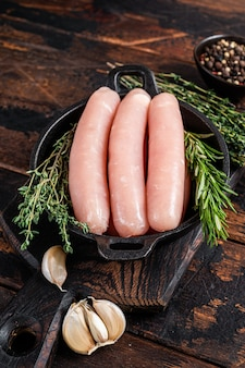 Pork raw sausages in a pan with herbs
