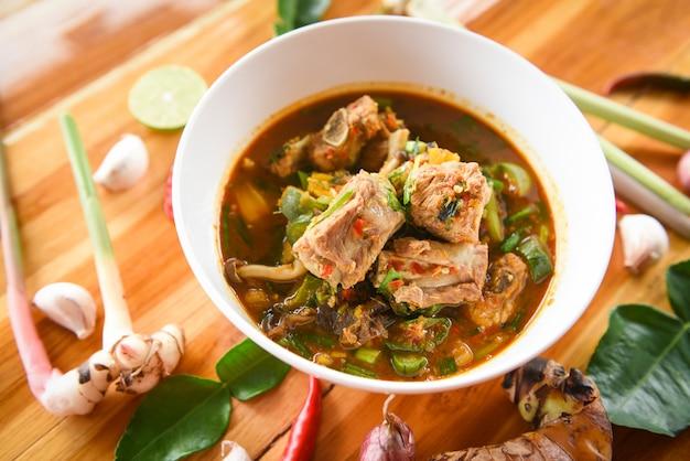 돼지 고기 갈비 카레 매운 스프 돼지 고기 뼈와 덥고 신 스프 그릇에 신선한 야채 톰 얌 타이 허브와 향신료 재료.
