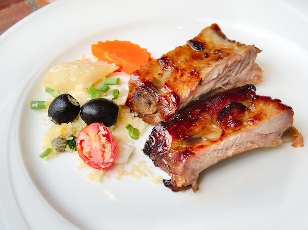 豚カルビをbbqソースで焼き、蜂蜜でカラメルにしたものを白いお皿に添えます。スライスしたバーベキューソースとバーベキューリブのクローズアップ。