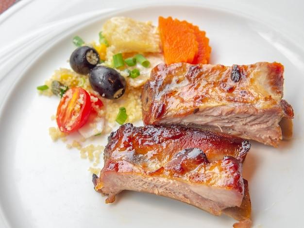 Свиные ребрышки на гриле с соусом bbq и карамелизированные в меде, подаются с гарниром на белой тарелке