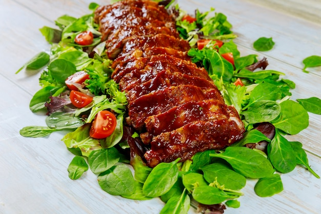 Свиные ребрышки на гриле с соусом барбекю, помидорами и шпинатом.