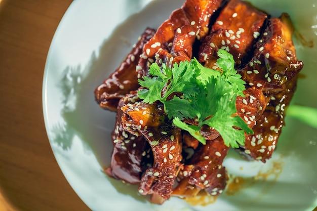 Свиные ребрышки в кисло-сладком соусе с кинзой, кунжутом и сычуаньским перцем в белой миске. китайская кухня