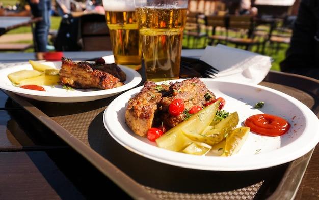 화창한 날에 트레이와 라이트 맥주 거리 음식 축제 음식에 돼지 갈비