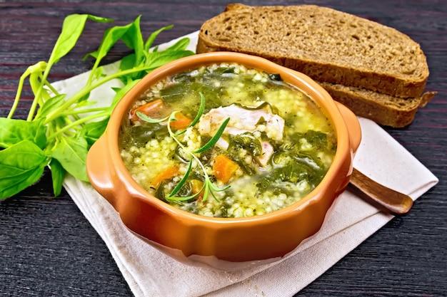 냅킨에 있는 점토 그릇에 쿠스쿠스와 시금치를 넣은 돼지 갈비 수프, 어두운 나무 판자 배경에 빵