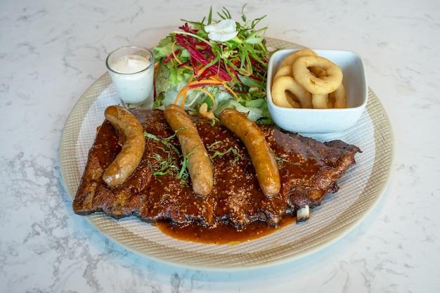 돼지 갈비 스테이크, 훈제 핫도그, 향기롭고 깊은 튀김 그리고 접시에 샐러드 야채.