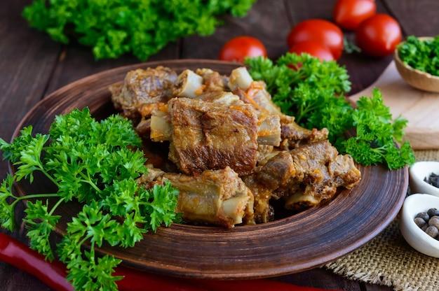 당근 찐 돼지 갈비, 파슬리 나무 배경에 점토 그릇에 장식. 확대