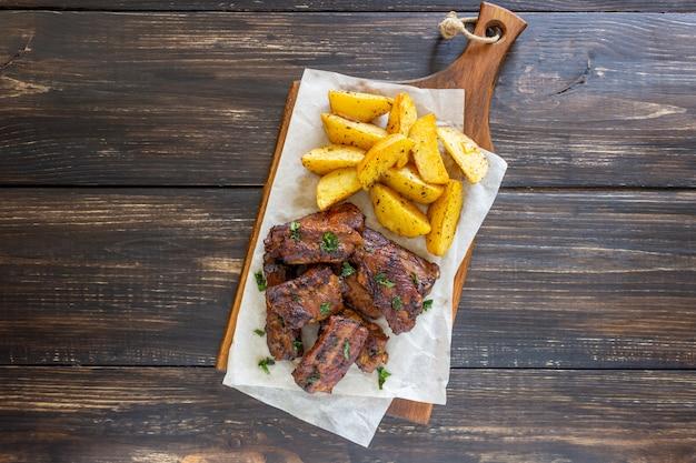 Свиные ребрышки с картофелем на деревянном столе. барбекю. гриль. американская кухня рецепт блюда.