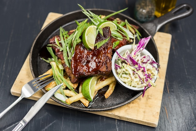Pork ribs with vegetables on a wooden table