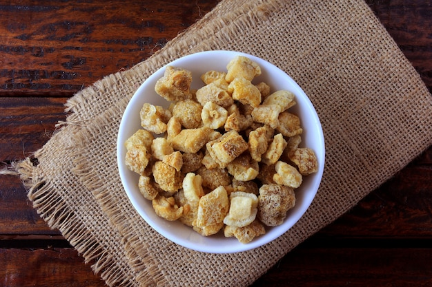 Pork rinds (torresmo) fried in ceramic bowl on rustic wooden table in restaurant. typical dish of brazilian and asian cuisine