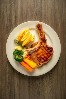 Стейк из свинины с овощами и чипсами.