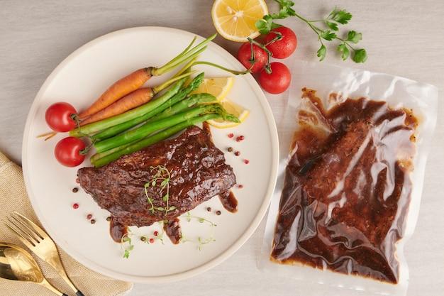 夏のバーベキューで焼いたスペアリブのポークローストに、野菜、アスパラガス、ベビーキャロット、フレッシュトマト、スパイスを添えて。石の表面に白いプレートの燻製リブ。上面図。