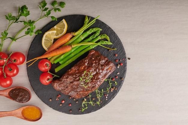 夏のバーベキューで焼いたスペアリブのポークローストに、野菜、アスパラガス、ベビーキャロット、フレッシュトマト、スパイスを添えて。黒い石の表面に燻製リブ。上面図、