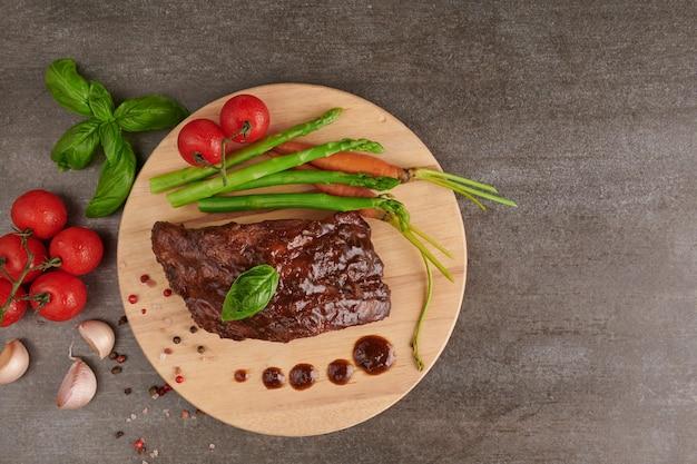 Жареные свиные ребрышки на гриле из летнего барбекю, подаются с овощами, спаржей, молодой морковью, свежими помидорами и специями. копченые ребра на деревянной разделочной доске на каменной поверхности. вид сверху.