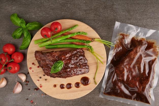 夏のバーベキューで焼いたスペアリブのポークローストに、野菜、アスパラガス、ベビーキャロット、フレッシュトマト、スパイスを添えて。石の表面の木製まな板の燻製リブ。上面図。