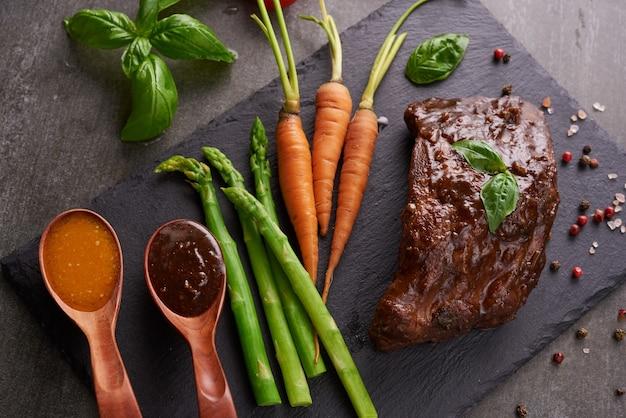 Costine di maiale arrosto e grigliate da un barbecue estivo servito con verdure, asparagi, carotine, pomodori freschi e spezie. costole affumicate su superficie in pietra nera. vista dall'alto,