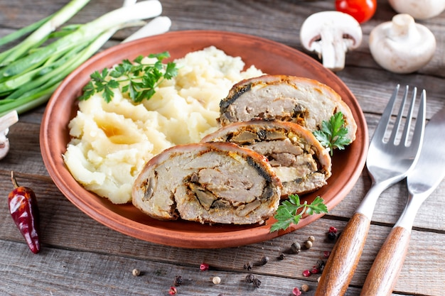 Рулет из свинины с грибами и сыром, подается с картофельным пюре на тарелке
