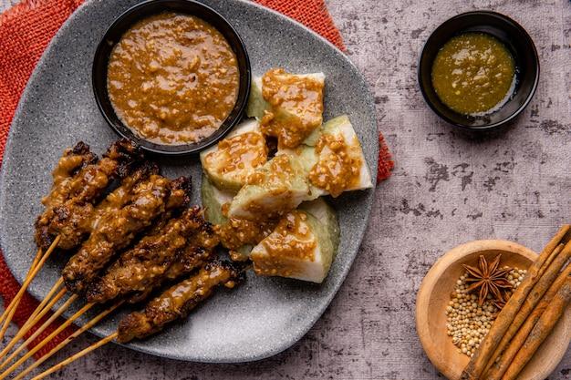 돼지 고기 satay 또는 sate babi 돼지 고기 satay와 땅콩 소스 및 lontong 또는 ketupat 떡 조각 제공