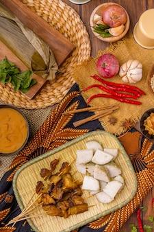 ポークサテまたはサテバビポークサテは、スパイシーなパダンソースと、バワンゴレンのカリカリ揚げエシャロットをふりかけたロントンまたはケトゥパットの餅のスライスを添えて提供されます