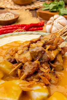 Pork satay or sate babi  pork satay served with a spicy  padang sauce and slices of lontong or ketupat rice cakes garnished with a sprinkle of bawang goreng crisp fried shallot