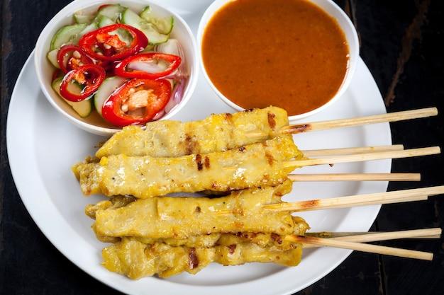 白いプレートにポークサテの串焼き竹と木製のテーブルにソース、タイのポークサテの屋台の食べ物。