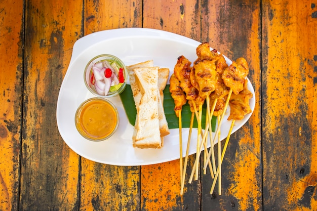 Pork satay with coconut milk and bread  with sauce in white plastic plate on wooden table.