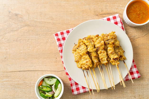 きゅうりのスライスと酢の玉ねぎであるピーナッツソースのピクルスとポークサテ-アジア料理のスタイル