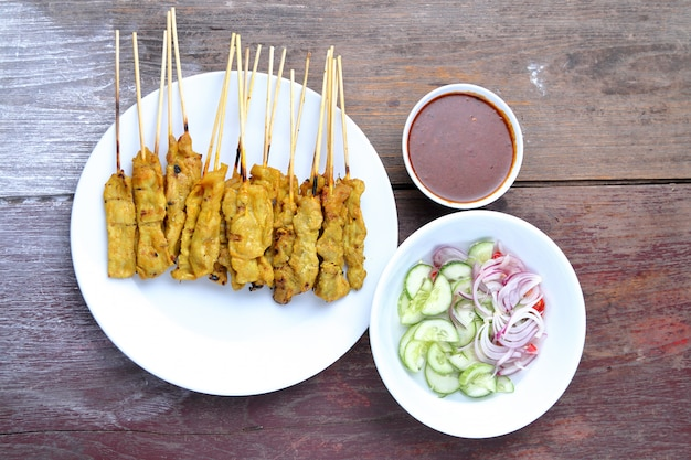 Pork satay with peanut sauce, wood table background.view from above.