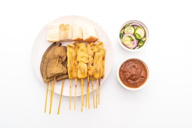 Свинина по-сатейски с арахисовым соусом и солеными огурцами, которые представляют собой ломтики огурца и лук в уксусе